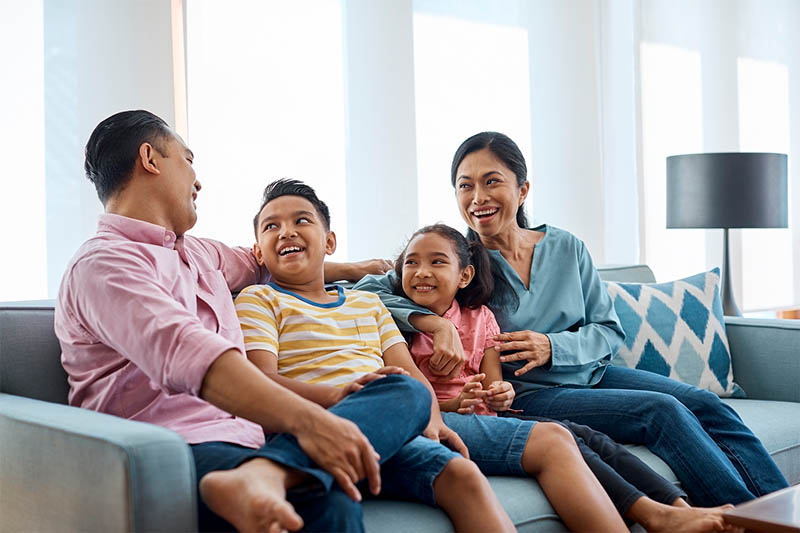 A family sitting together on sofa and smiling